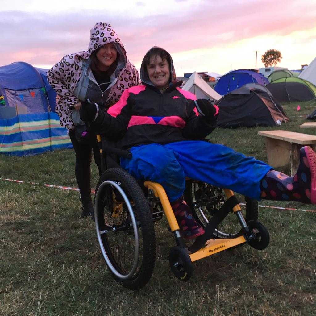 A photo of Jess in her yellow all terrain wheelchair. Jess is wearing waterproof blue trousers and a pink and black rain jacket. She is smiling with her friend who is wearing a pink animal raincoat behind her. Behind them both are lots of differently coloured tents.