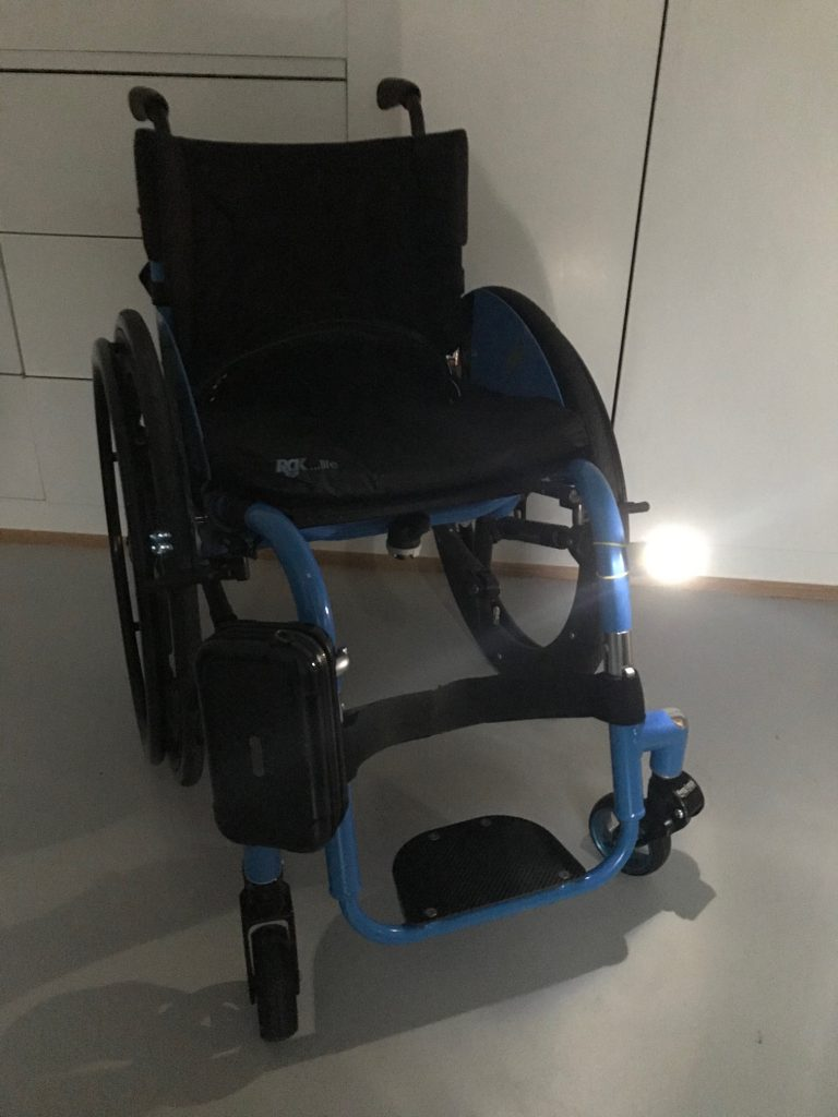 A photo of a blue wheelchair, with a bright white light on the front of the frame.