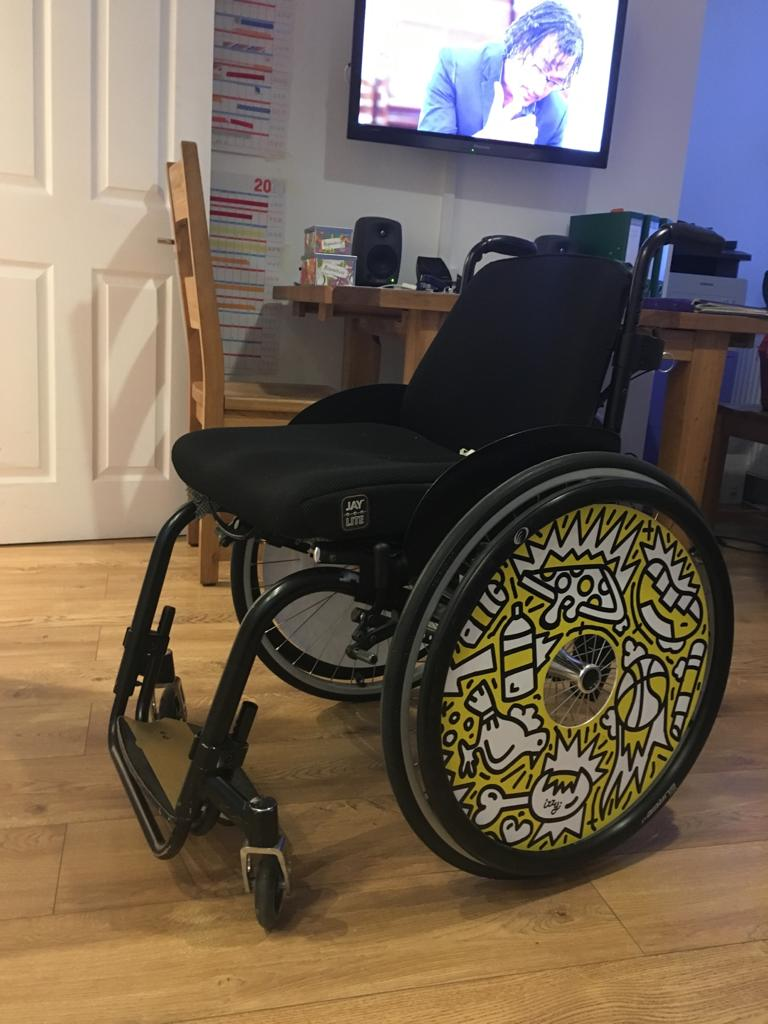 A photo of a black wheelchair which has bright patterned yellow and white wheel covers on it.