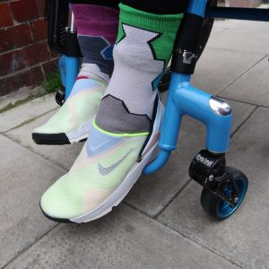 A photograph showing Nike's new Go Fly Ease - hands free trainers on Touretteshero's feet, the frame and footplate of a sleek bright blue wheelchair is also visible. The trainers are pale colours and made of a fly knit material that has a gentle ribbed texture. Alongside the fresh trainers Touretteshero is also wearing patterned socks in colours that vaguely match the shoes.