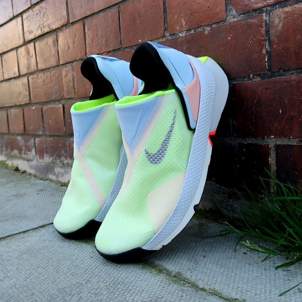 A photograph showing Nike's new Go Fly Ease - hands free trainers. The shoes are hinged and this photo shows them in the closed position propped up against a brick wall. The trainers are pale colours and made of a fly knit material that has a gentle ribbed texture.
