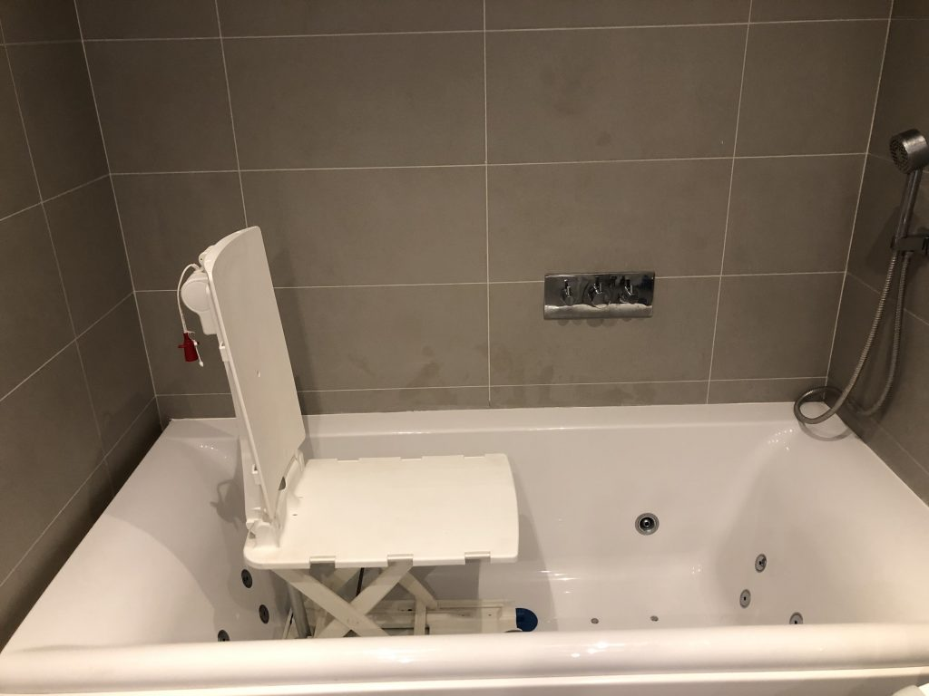 This is an image of large white jacuzzi bath with a chair lift. It is surrounded by large grey tiled walls.