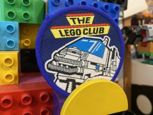 A photo of a circular, iron on Lego Club patch from around 1985 - the patch features a chunky vehicle with tubes coming from it and Lego Club written in Capital letters in an assertive font.,