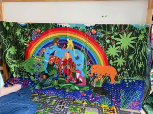 A photograph of Bean's new blanket. It is a colourful drawing by Touretteshero of her niece Bean surrounded by animals in a jungle-like scene. The drawing has been printed onto a blanket which is hanging over her bed. In the drawing, Bean can be seen standing in the centre of the image wearing a red and black polka dot jumpsuit surround by all kinds of animals such as a tiger, an elephant, a fox, a peacock, 2 toucans, 4 monkeys. Bean and the animals are standing under a big bright rainbow.