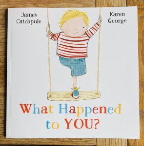 A photograph of the front cover a children's book titled 'What Happened to You?' by James Catchpole and Karen George. The book is square and white with an illustration of a boy with one leg standing on a wooden swing in the centre of the front cover. He is wearing a striped white and red shirt, blue trainers and hatched blue shorts. The little boy is smiling and winking.