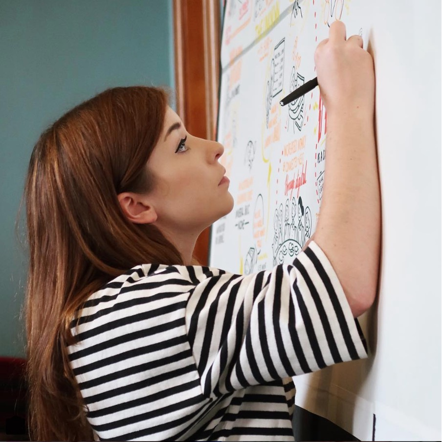A photograph of illustrator and live scribe Amber Anderson. Amber is a white woman in her thirties with long red hair. She is wearing a black and white striped t-shirt and is holding a marker pen in her right hand, drawing on a large upright whiteboard.