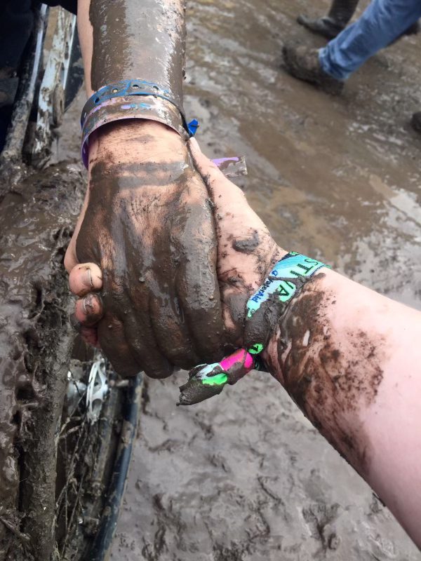 A close up photograph of a pair of muddy hands, clasped together as a wheelchair user is pulled through the mud at a festival