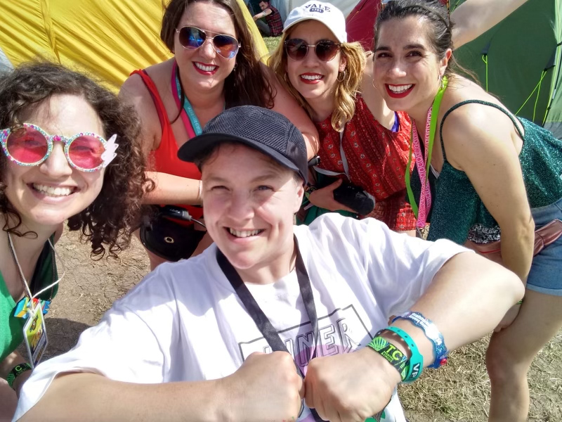 Touretteshero is at the centre of an image grinning at the camera a team of four friends and personal assistants is gathered around her, all are dressed for a festival and wearing lanyards, tents are visible in the background, gentle sunlight falls across their joyful faces