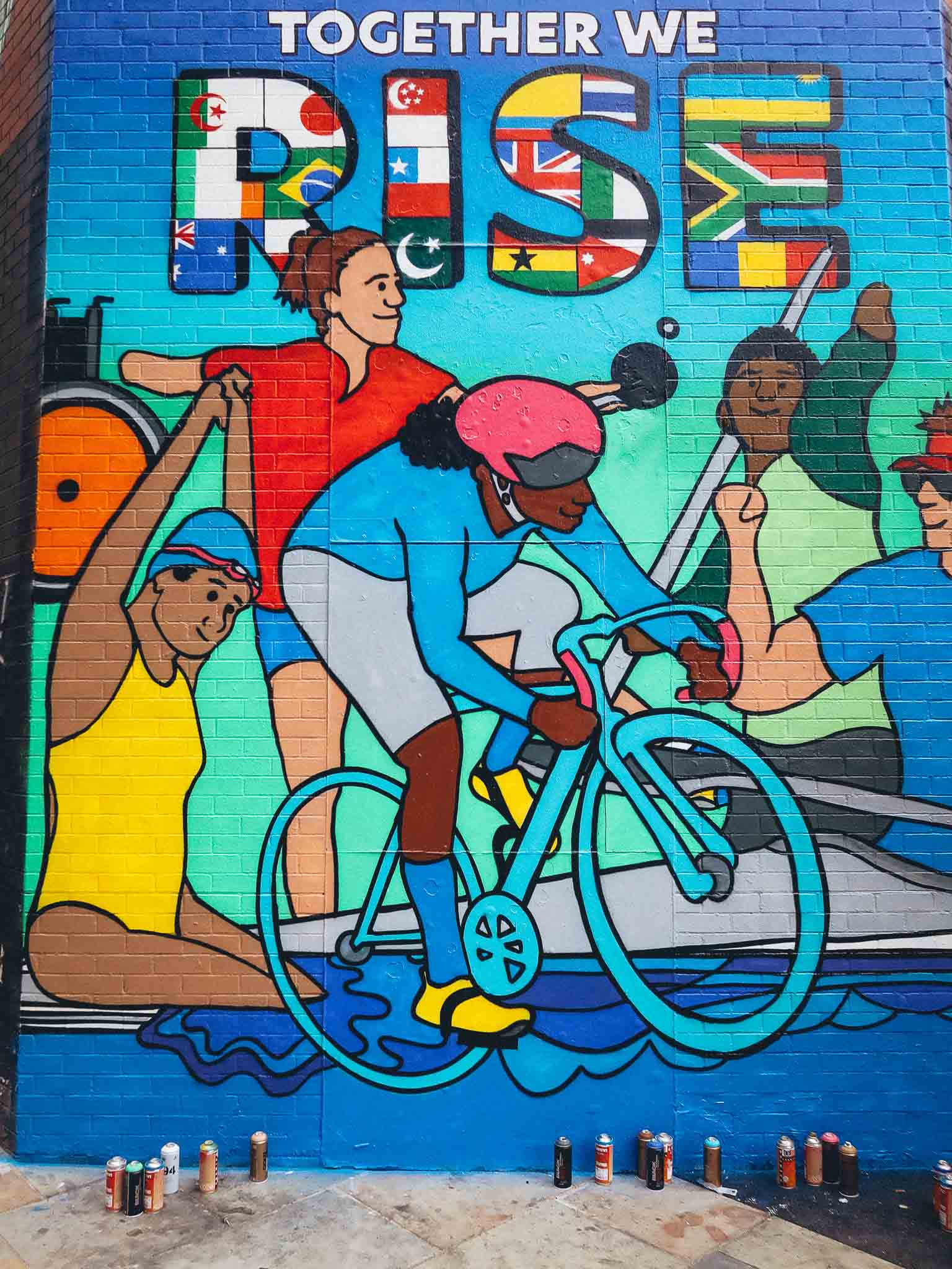 A photograph of Jess's Citibank Paralympics Mural painted on a corner in Shoreditch in London by art collective Graffiti Life. The mural is in a colourful bold graphic style and depicts Paralympian's taking part in their various sports such as canoeing, cycling, table tennis and swimming. At the top of the mural there is text which reads 'Together We Rise'. The capitalised font of the word 'Rise' contains flags of the countries from all over the world including Ireland, Australia, Japan, Ecuador and South Africa.