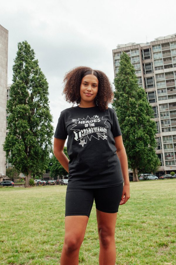A photograph of Ines, a woman in her late teens modelling a black Touretteshero Heroes of the Imagination t-shirt. She is looking at the camera smiling and is standing in a green field with tower blocks in the background.