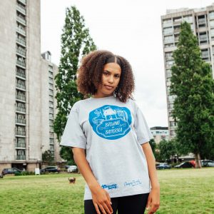 A photograph of Ines, a woman in her late teens modelling a grey Touretteshero Heroes 'Brewing in Battersea' t-shirt. She is looking at the camera smiling and is standing in a green field with tower blocks in the background.