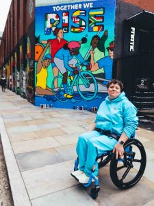 A photograph of Jess in front of the mural she designed for Citibank's partnership with the Tokyo Paralympics in Shoreditch. Jess is a white woman in her forties with short curly brown hair wearing an aqua blue matching tracksuit and nike fly ease trainers. She is using a blue RGK wheelchair. In the background the mural, which was painted by street art collective Graffiti Life is in a bold graphic style.